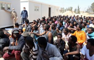 Migrants from sub-Saharan Africa sit at a center for illegal migrants in the al-Karem district of the Libyan eastern port city of Misrata on April 15, 2015, after their boat was intercepted by the Libyan coast guard. AFP PHOTO / MAHMUD TURKIA