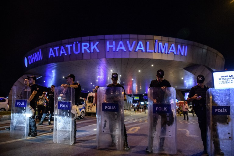 Turkish anti riot police officers block the main enterance of the Ataturk airport in Istanbul June 28, 2016 after two explosions followed by gunfire hit Turkey's biggest airport, killing at least 28 people and injuring 20. All flights at Istanbul's Ataturk international airport were suspended on June 28, 2016 after a suicide attack left at least 10 people dead and 20 others wounded, Turkish television stations reported. / AFP PHOTO / OZAN KOSE